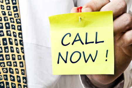 Call now post it in business man hand