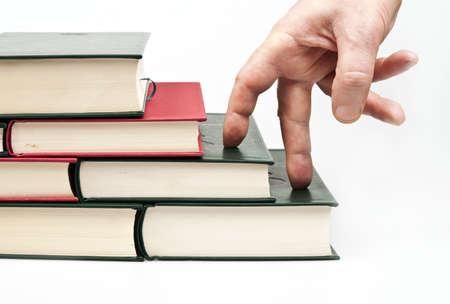 Finger climbing books on white