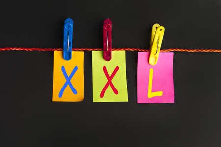 XXL word on laundry hook on black background