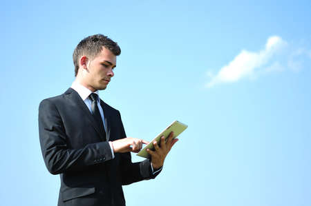 Business man with tablet on sky