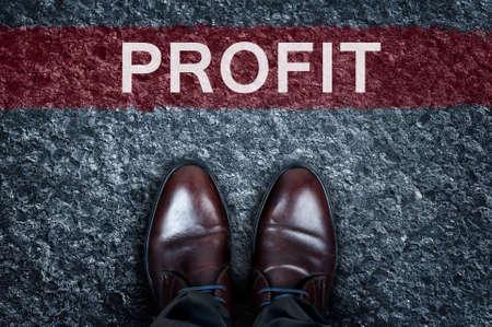 Profit message on asphalt and business shoes
