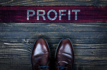 Profit message and business shoes on wooden floor