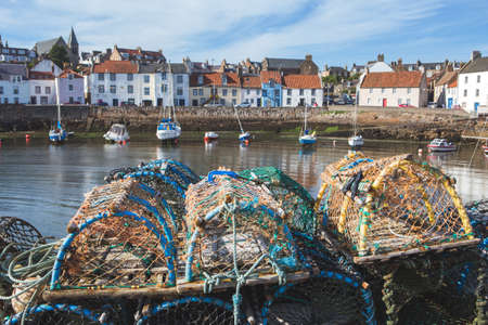 Photo pour Traditional lobster pots/crab pots and small fishing boats in the East Neuk of FIfe fishing village of Pittenweem, Scotland - image libre de droit