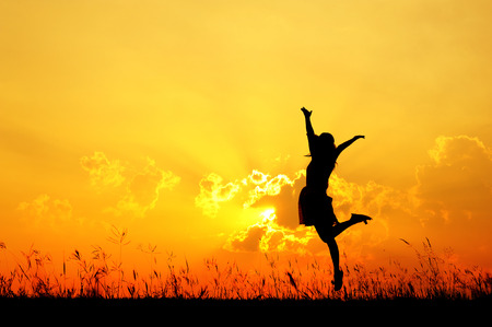Photo for Woman jump and sunset silhouette when she happy - Royalty Free Image