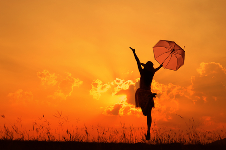 Photo for Umbrella woman jumping and sunset silhouette - Royalty Free Image