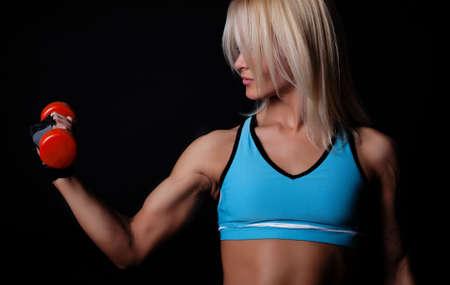 Foto de Portrait of a sportswoman lifting heavy dumbbells in dark gym room - Imagen libre de derechos
