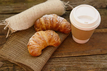 Two croissants and coffee-to-go in a rustic setting