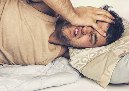 Photo pour Young man  in bed , trying to sleep - image libre de droit