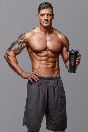 Muscular man with tattos posing in studio