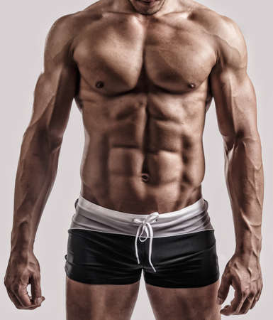 Photo pour Portrait in studio of muscular male body in black swimming trunks. Isolated on grey background. - image libre de droit