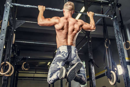 Shirtless man pulling up on horizontal bar in a gym.
