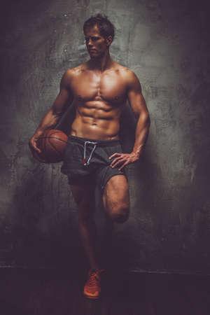 Shirtless basketball player posing over grey wall.
