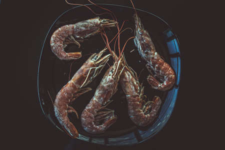 Tiger shrimps on glance black plate.