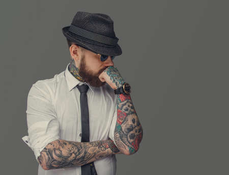 Photo pour Man with tattooed arms thinking. Isolated on grey background. - image libre de droit