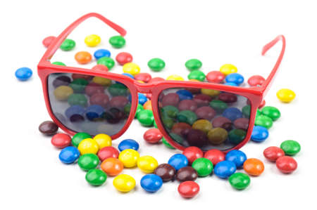 Red sunglasses and colorful candys isolated on white background.