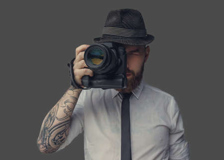 Photo pour Digital photographer in white shirt and casual hat. Isolated on grey background. - image libre de droit