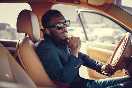 Photo pour Blackman in sunglasses driving a car. - image libre de droit