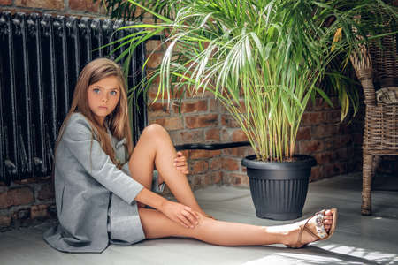 An attractive blonde teenage girl sits on the floor near the pot with green plants.