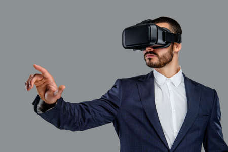 Photo pour Portrait of bearded male in a suit with virtual reality glasses on his head isolated on grey background. - image libre de droit