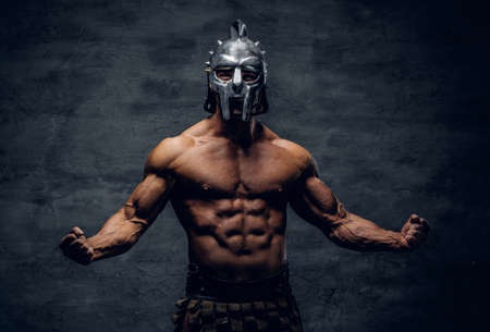 Foto de Brutal shirtless muscular male in a gladiator silver helmet on grey background. - Imagen libre de derechos