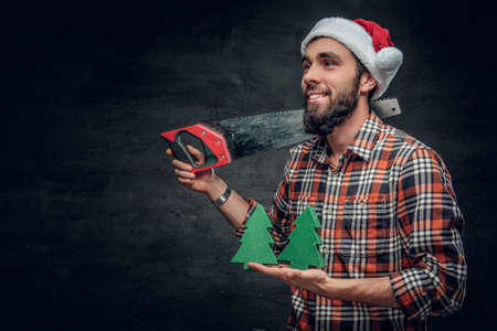 Positive bearded male in Santa's hat holds small fir trees and handsaw on a shoulder.