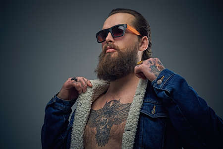 Portrait of bearded male in sunglasses with tattoo on a chest wearing a denim jacket.