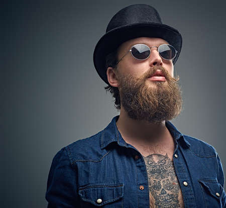 Studio portrait of stylish bearded male with a tattoo on his chest, dressed in a denim shirt, cylinder hat and sunglasses isolated on grey background.