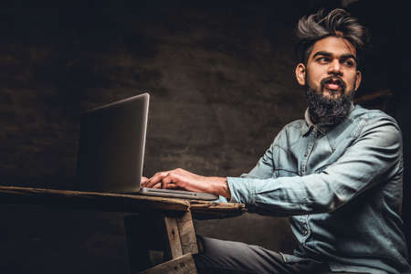 Stylish bearded Indian male working with laptop.