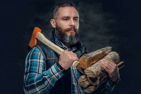 Bearded middle age male holds an axe and firewoods over dark grey background.