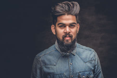 Portrait of stylish bearded Indian male dressed in a denim jacket.