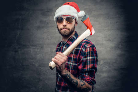 Portrait of a bearded man wearing Santa's hat and holds axe.