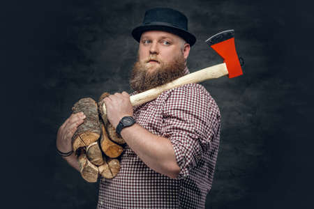 Fat bald, bearded man holds an axe and fire woods.