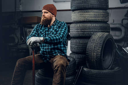 The brutal bearded mechanic male sits on an old tire in a garage.