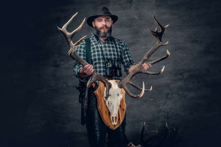 The bearded hunter male holds a skull of a deer.
