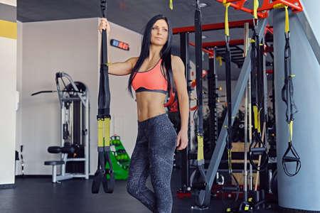 Slim sporty female posing near trx straps stand in a gym club.