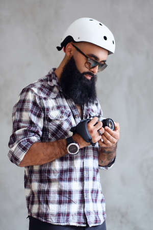 A bearded hipster amateur photographer with tattoos on arms, dressed in a fleece shirt holds compact DSLR camera over grey background.