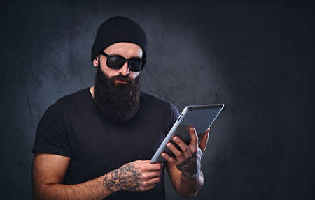 Bearded brutal male in a hat and sunglasses holds tablet PC over grey background.