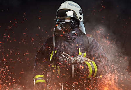 Photo for A firefighter dressed in a uniform in a studio. - Royalty Free Image
