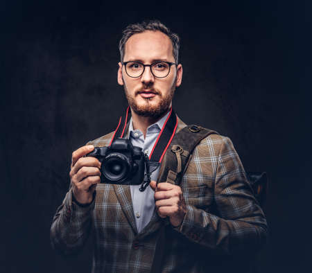Traveler and photographer. Studio portrait of a handsome bearded man