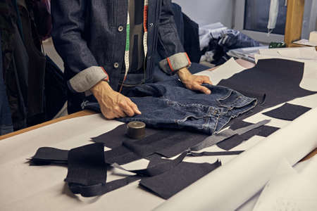 ropped image of a tailor working with jeans material at sewing workshop.
