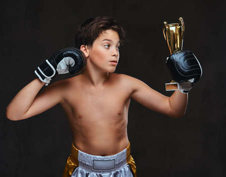 Young shirtless boxer champion wearing gloves holds a winners cup showing muscles.