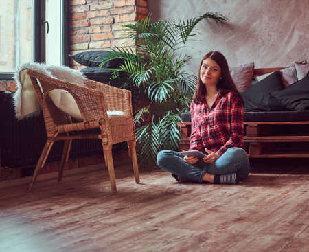 Charming brunette girl student dressed in a plaid shirt and jeans holding digital tablet sitting on a floor in a room with loft interior.