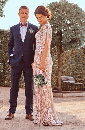 Foto de Full body portrait of beautiful newlyweds - charming bride with her handsome groom posing in the park on sunny day. - Imagen libre de derechos