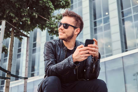 Smiling young man in sunglasses with stylish hair dressed in black leather jacket holds smartphone while sitting near a skyscraper.