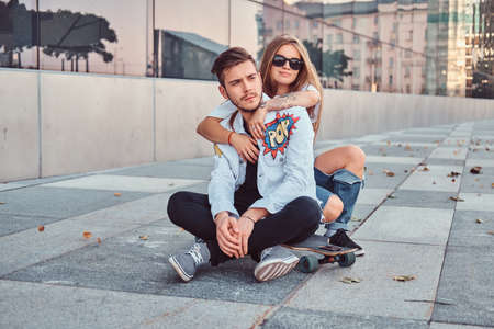 Trendy dressed young couple - pretty girl embrace her boyfriend while they sitting together on a skateboard near skyscraper.