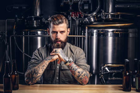 Photo pour Portrait of a pensive tattooed hipster male with stylish beard and hair in the shirt in indie brewery. - image libre de droit