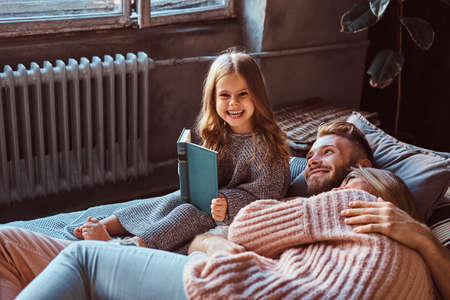 Photo pour Mom, dad and daughter reading storybook together while lying on bed. - image libre de droit