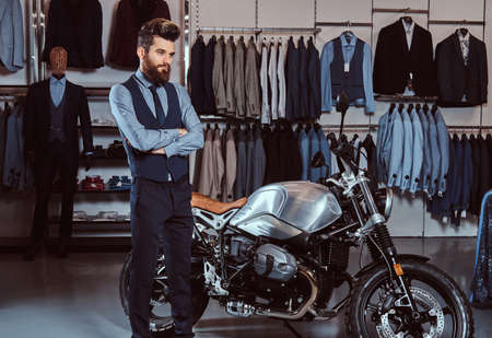 Elegantly dressed man posing with crossed arms near retro sports motorbike at the mens clothing store.