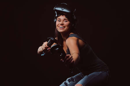 Confident young woman wearing virtual reality glasses and holds joysticks, posing at camera.