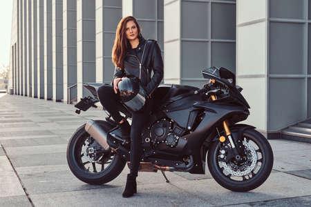 Foto de A beautiful biker girl leaning on her superbike outside a building. - Imagen libre de derechos